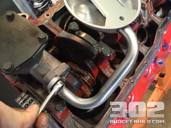 Tighten oil pump screen to oil pump with a 1/2 wrench