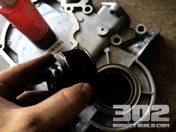 Timing cover front seal shown. Use an oil filter wrench to evenly distribute pressure while setting the seal.